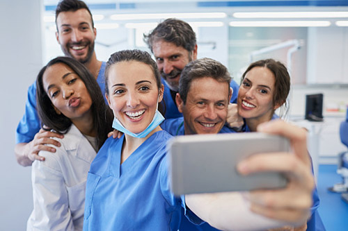 dentist and dental staff pose for a selfie
